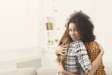 Woman with sly facial expression embracing lfriend