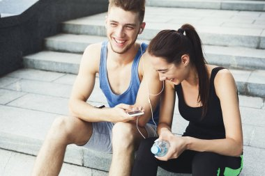 Woman and man laughing and listening music after jogging
