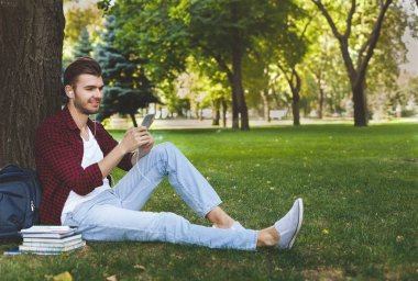 Young man listening to music on the grass outdoors