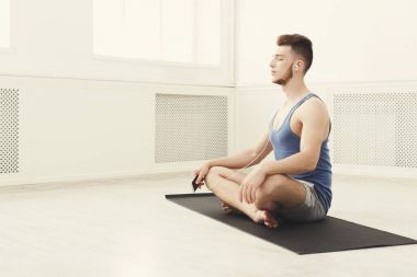 Man training yoga in lotus pose, copy space