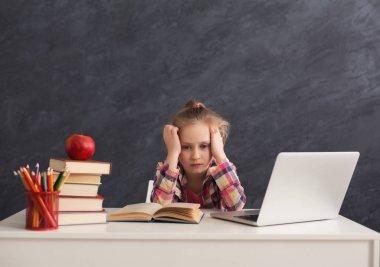 Tired little girl doing homework on laptop