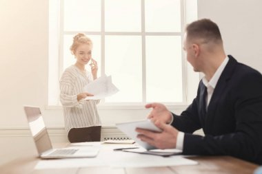 Male and female managers working on financial papers at modern office interior