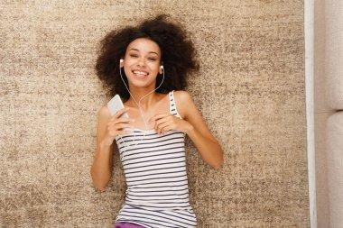 Happy young woman in earphones on floor