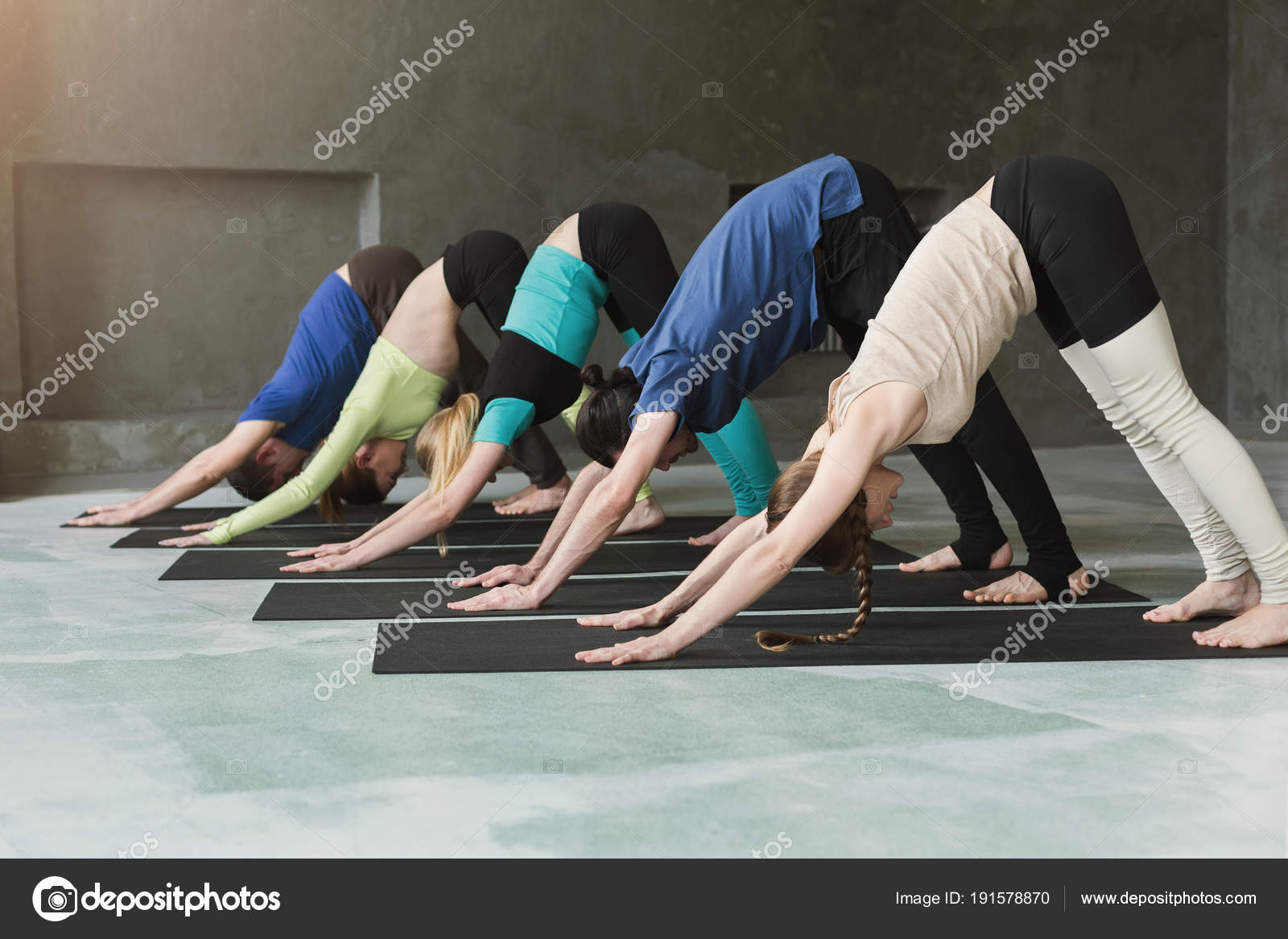 Young Women And Men In Yoga Class Doing Stretching Exercises Stock Photo