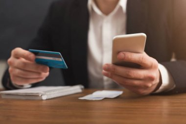 Mans hands holding a credit card and using smartphone