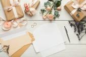 Svatební pozvánky a obálky na bílý dřevěný stůl, na