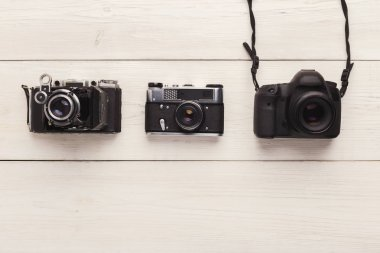 Three different photo cameras on white table, top view. Comparison of different generations of photographing equipment. Technology progress concept, copy space stock vector