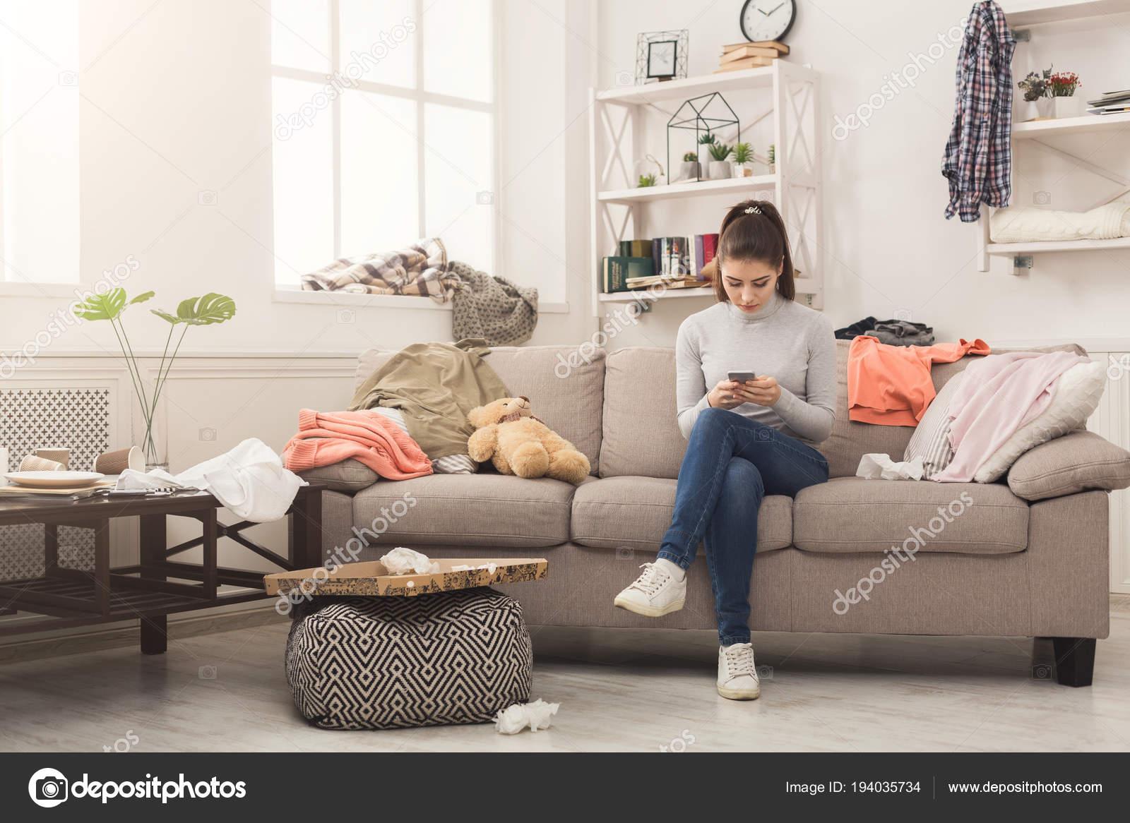 Wanhopige vrouw zittend op de Bank in rommelige kamer — Stockfoto ...