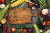 Fresh organic vegetables and wooden board background