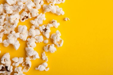 Slaty popcorn scattered on yellow background, top view