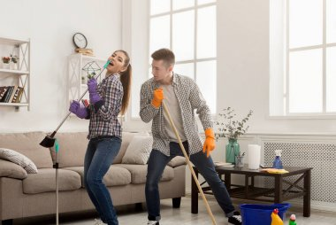 Young couple cleaning home, having fun