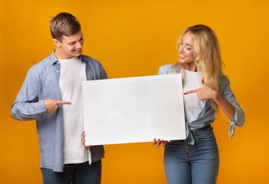 Millennial couple holding blank advertising board and pointing on it