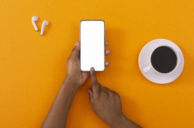 Female hands touching cellphone with blank screen on orange background
