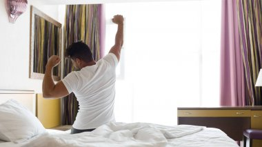 Man stretching in bed after waking up in hotel room, panorama with copy space stock vector