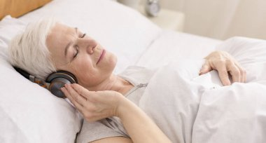 Calm senior woman in headphones enjoying audiobook