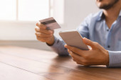 Unrecognizable man using smartphone and credit card, purchasing goods online