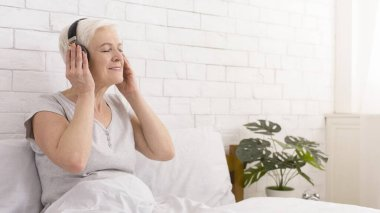 Peaceful senior woman listening to motivational audio tutorial