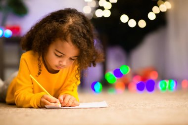 Little black girl drawing on floor near xmas tree