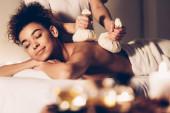 Mladá žena dostává masáž s lázeňskými bylinnými kuličkami