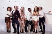 Pozitív fiatalok állnak alatt Falling Confetti szórakozás beltéri