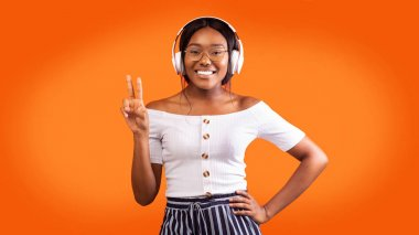 Smiling Afro Lady In Wireless Headphones Gesturing Victory Sign, Studio