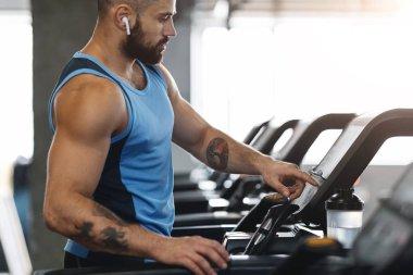 Muscular man in modern wireless headphones running