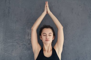 Woman practicing yoga and meditating with closed eyes
