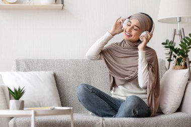 Relaxed Muslim Girl In Hijab Listening Music With Wireless Headphones