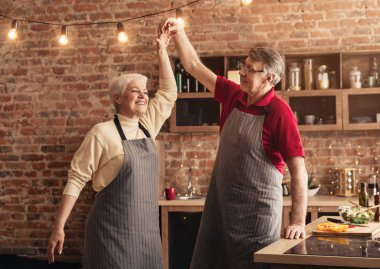 Happy senior couple dancing at kitchen, free space