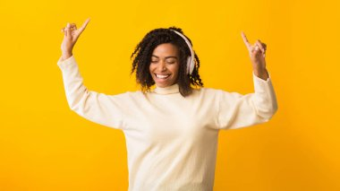 Smiling afro woman listening to music and dancing