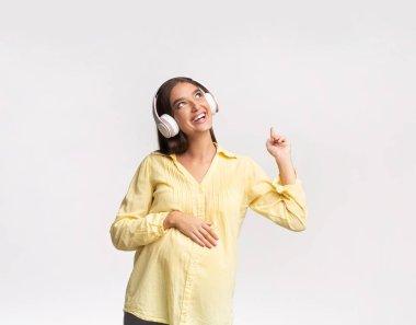 Cheerful Pregnant Girl Listening To Music In Headphones In Studio