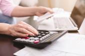 Idősebb nő adószámítás otthon, számológép segítségével