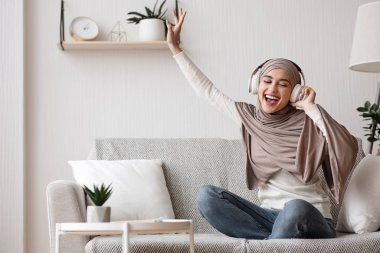 Joyful muslim girl enjoying listening music in wireless headphones at home