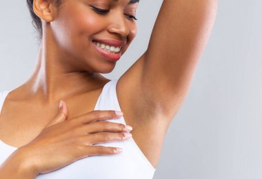 Close up of happy afro girl smelling her armpit