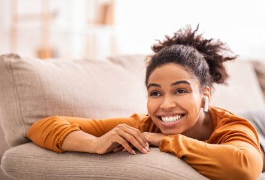 Happy Black Woman In Earbuds Listening To Music Relaxing Lying On Sofa Enjoying Weekend At Home. Selective Focus stock vector