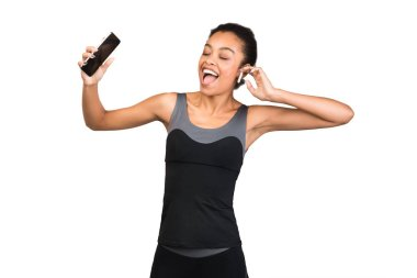 Happy Girl With Smartphone Listening To Workout Music, Studio Shot