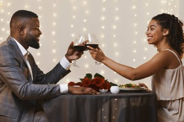 Handsome black man and pretty afro woman drinking wine at restaurant, toasting and celebrating Valentines Day, copy space stock vector