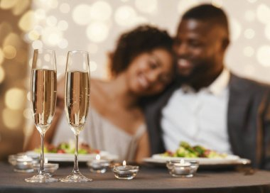 Lovely black couple celebrating St. Valentines Day at restaurant, selective focus on two glasses of champagne stock vector