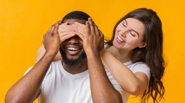 Guess who. Playful young woman covering her boyfriends eyes from behind, surprising him, yellow studio bakground, panorama with free space stock vector