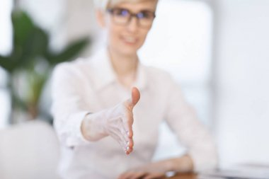 Businesswoman Stretching Hand For Greeting Sitting In Office, Shallow Depth