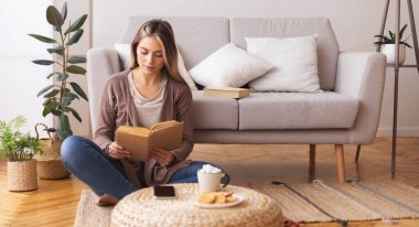Young woman reading book, sitting on floor at home