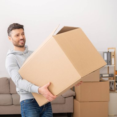 Man transferring heavy box while moving in new apartment