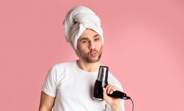 Guy blowing in hairdryer with towel on his head