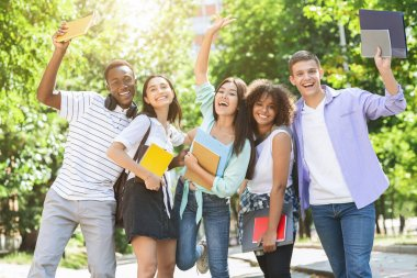 Portrait of joyful college students posing outdoors after passing exam
