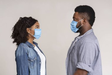 Virus Alert. Frightened Black Man And Woman In Sterile Medical Masks Looking At Each Other While Standing Together Over Light Background, Side View stock vector
