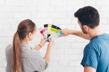 Young couple looking at color samples at home