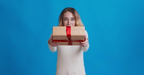 Vidám fiatal nő ajándékdobozt kínál a kamerának és mosolyog
