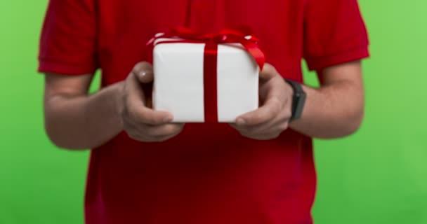 Muž na zelené obrazovce chroma klíč pozadí drží dar