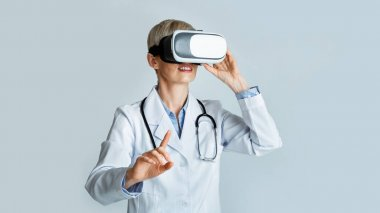 Virtual training for medical workers. Woman doctor in virtual reality glasses points finger