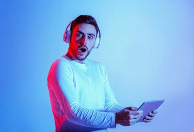 Shock concept. Millennial guy in headphones with open mouth and holding tablet